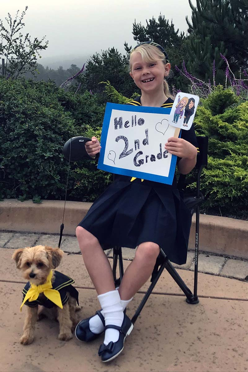 Santa Catalina Lower and Middle School second grader holding up a first day of school sign with her dog