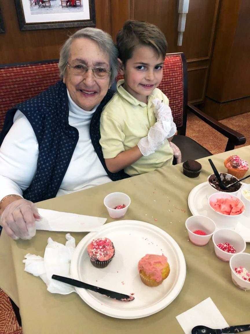Senior and boy smiling with cupcakes