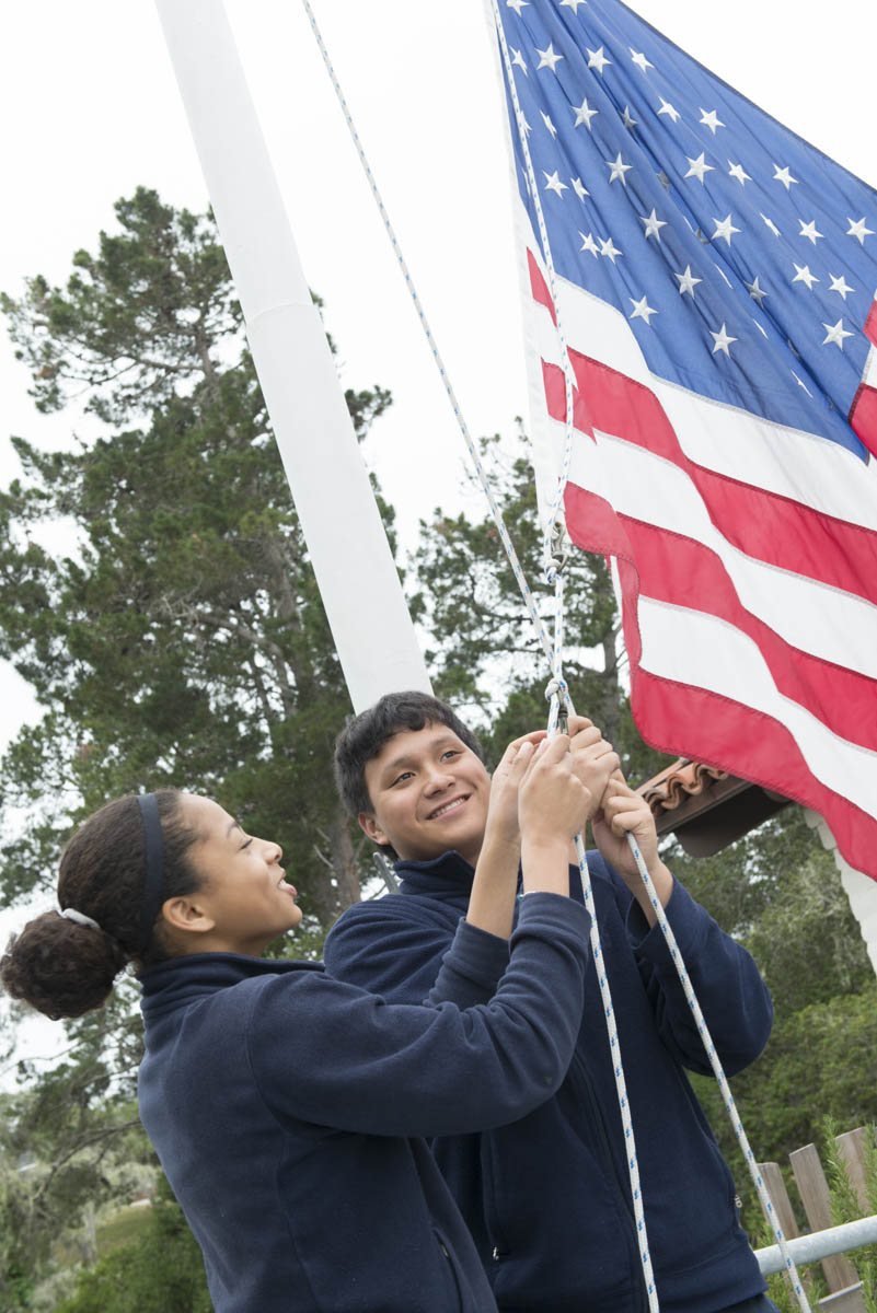 Girl and boy raising American flag