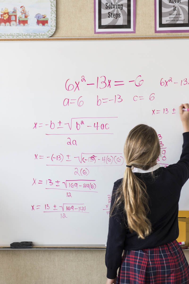 Girl writing equations on whiteboard