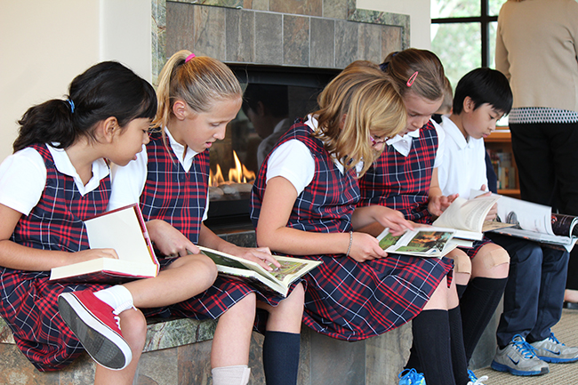 Girls reading in front of fireplace